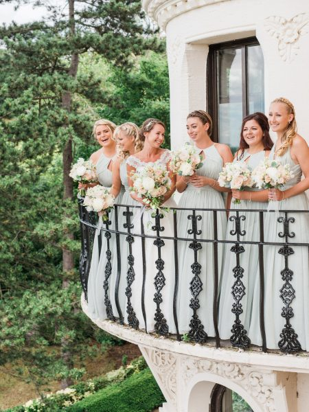 Bride and Bridesmaids in soft aqua green dresses stand on a turret balance for a portrait holding their blush and cream antique rose and peony relaxed wedding flowers bouquet from Fairy Nuff flower for a London wedding