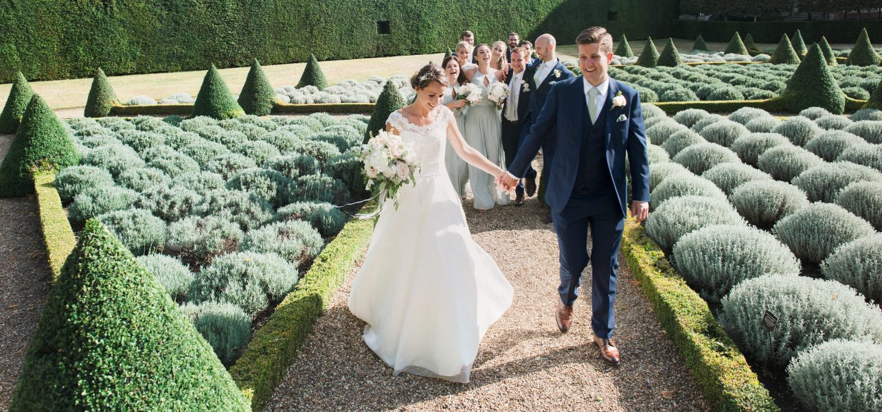 Post ceremony portrait of Bride and Groom walking through an elegant topiary garden leading their merry bridal party behind them for a London wedding
