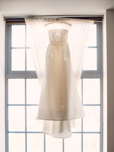 Elegant wedding dress hanging in a window pre wedding ceremony