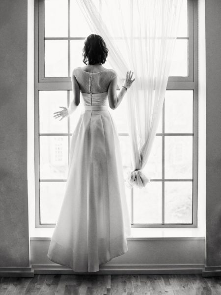 Elegant Black and White Fine Art portrait of a London Bride standing with her back to the camera looking out of a window pre wedding ceremony