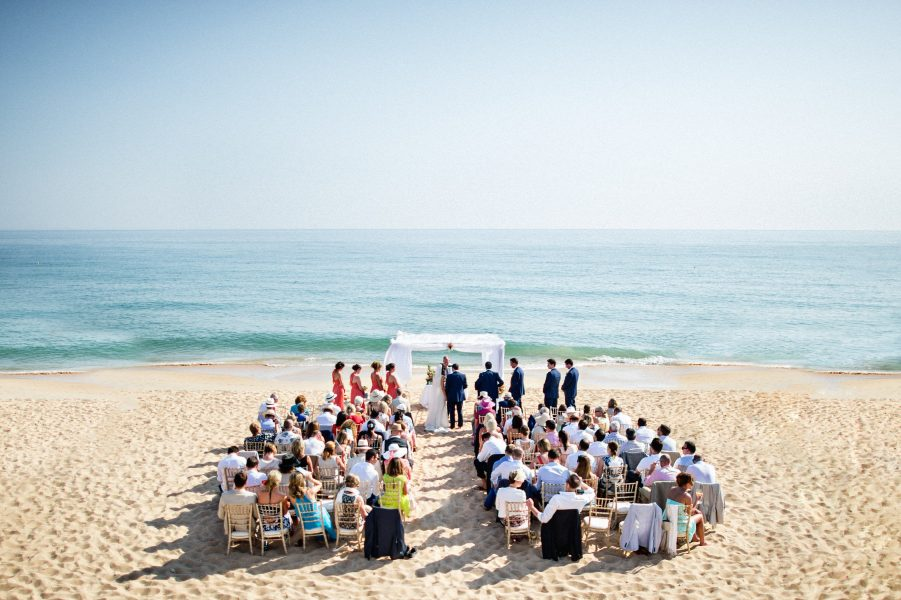 Aerial landscape image of outdoor beach wedding ceremony with sea and sand backdrop Algarve Portugal