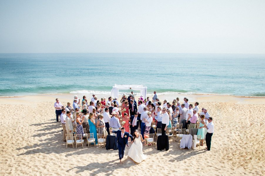 Aerial landscape image of Bride and Groom skipping down the aisle after their outdoor beach wedding ceremony with sea and sand backdrop Algarve Portugal