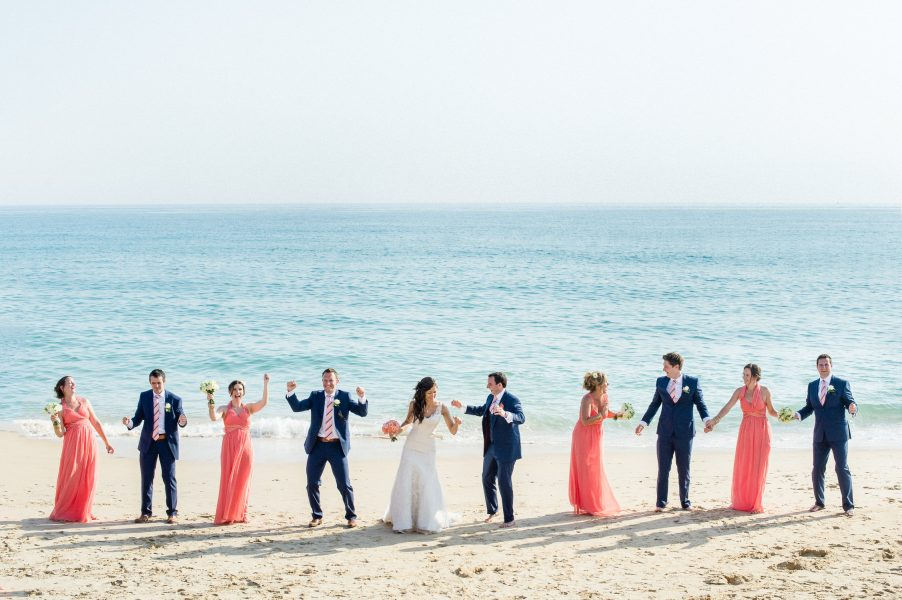 Relaxed natural Bridal portrait photo of Bridal party in coral dresses and Groomsmen in navy suits with Bride and Groom in the middle surrounded by a backdrop of sea and sand Algarve Portugal