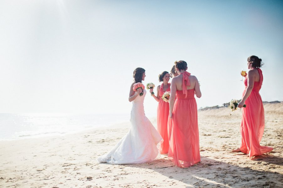 Relaxed natural Bride with the maids in coral dresses surrounded by a backdrop of sea and sand Algarve Portugal