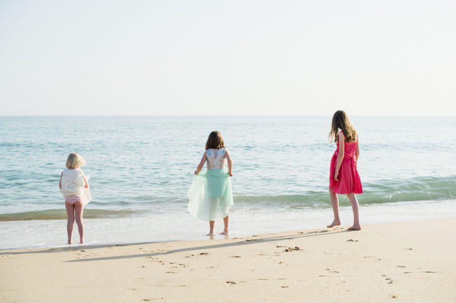 Youg children guests play at the edge of the sea at the Algarve Portugal wedding