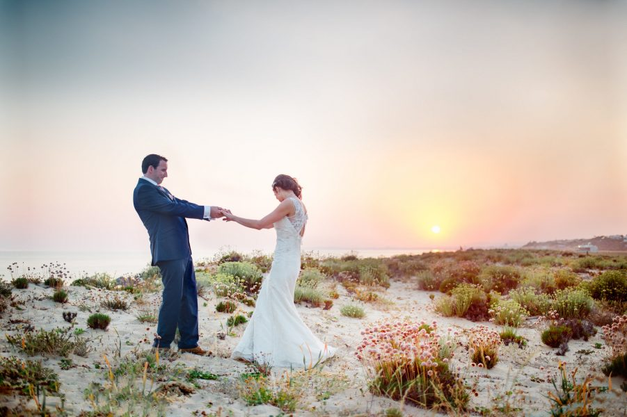 Relaxed natural Bridal portrait Bride and Groom pulling each other in a fun playful moment as the sunsets in the background over the sea Algarve Portugal