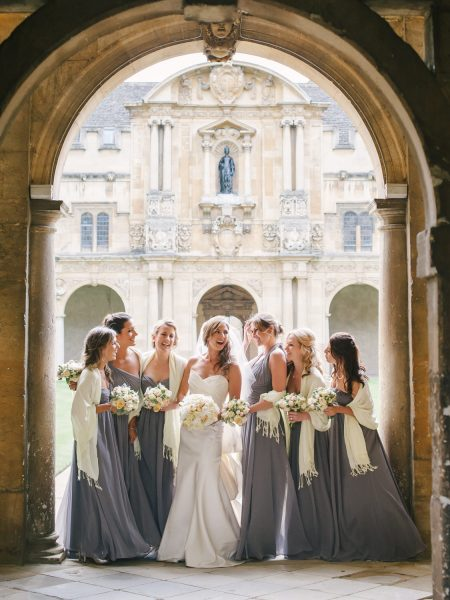 Fine Art Portrait of Bride surrounded by bridesmaids in long grey dresses standing in an Oxford University Archway in a sculptural dress Bodleian Library wedding for a chic Oxford wedding