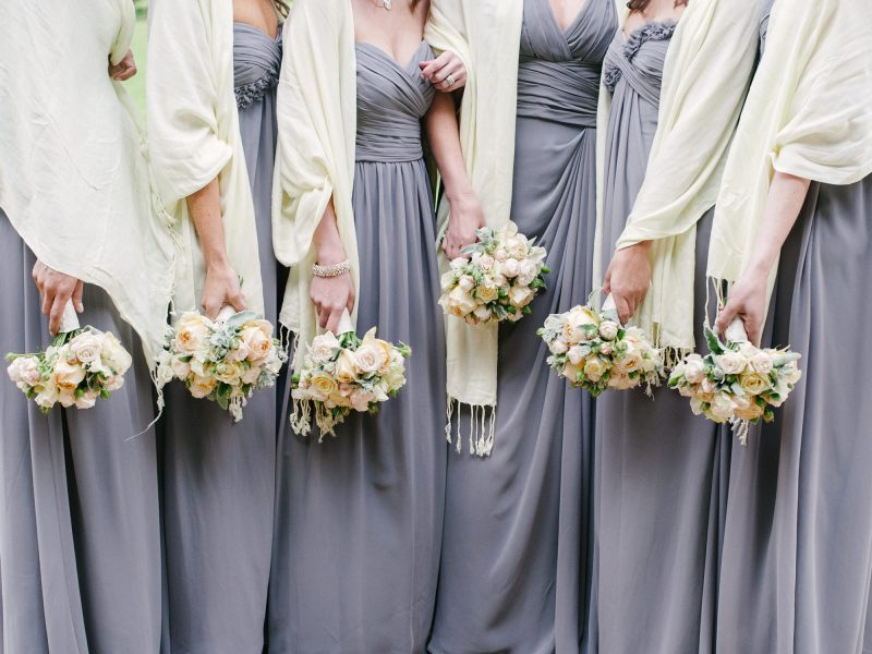 Fine Art Portrait of Bridesmaids from the neck down holding soft apricot and cream bouquets in long grey dresses for a chic Oxford wedding