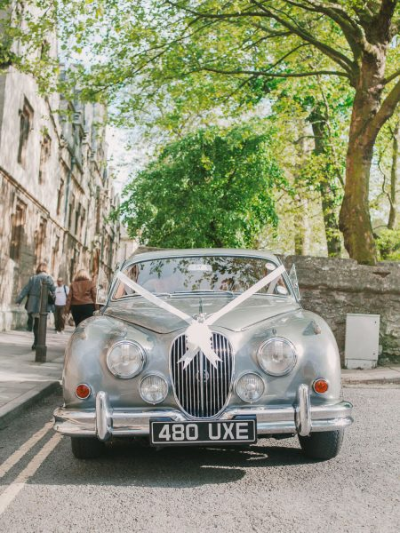 Silver vintage Jaguar wedding car under green trees