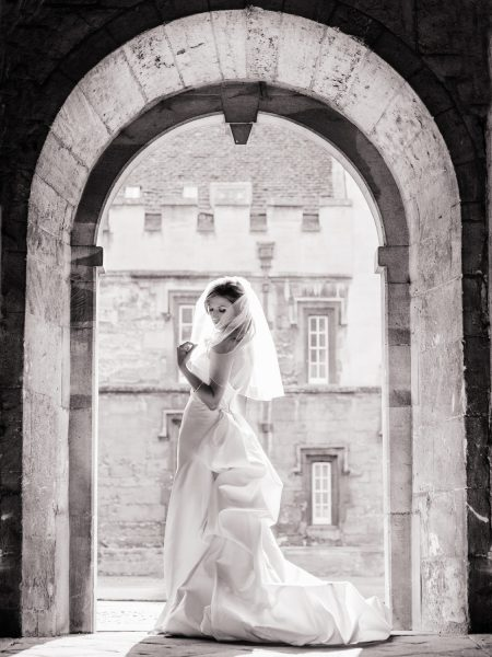 Fine Art Portrait of Bride in Oxford University Archway in a sculptural dress Bodleian Library wedding for a chic Oxford wedding