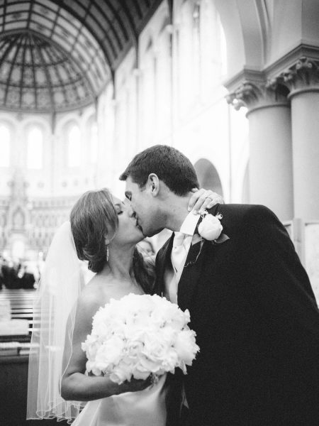 Fine Art Portrait of Bride and Groom kissing in a candid post ceremony moment in The Oratory church before their Bodleian Library wedding reception for a chic Oxford wedding