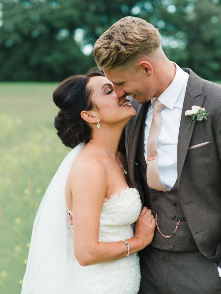 Stylish Surrey wedding couple kiss in a buttercup meadow at Botley Mansion Surrey
