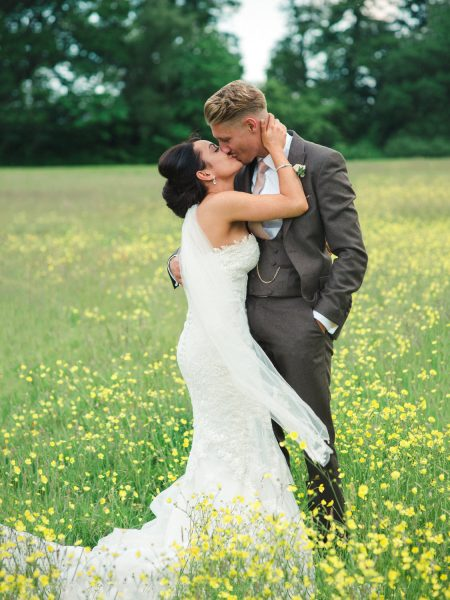 Full length portrait of a stylish Surrey wedding couple kiss in a buttercup meadow at Botley Mansion Surrey