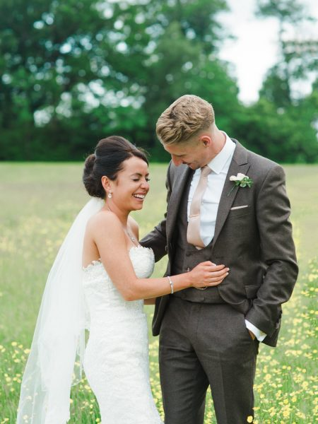 Stylish Surrey wedding couple laugh together in a buttercup meadow at Botley Mansion Surrey