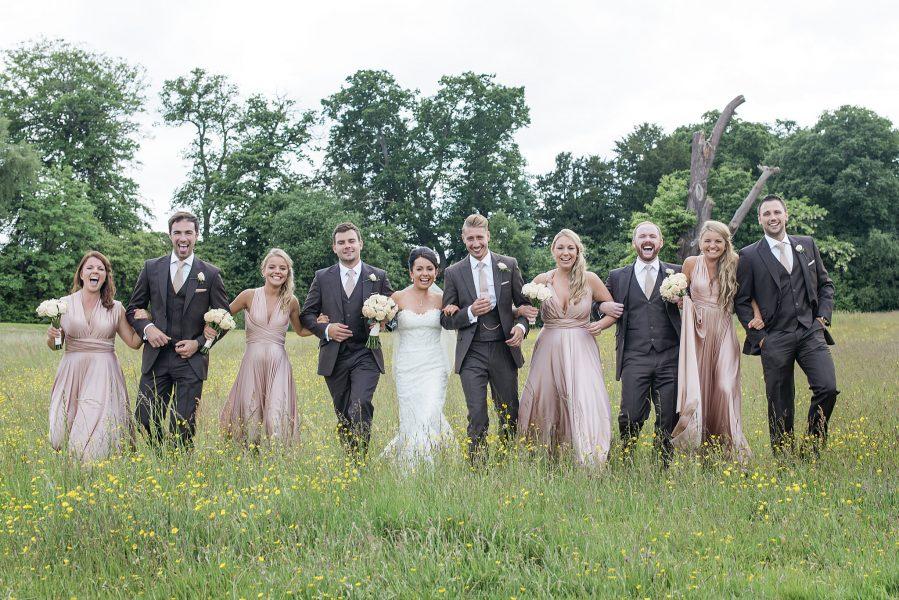 Bridal party walk towards the camera linking arms smiling away in a buttercup meadow at Botley Mansion Surrey