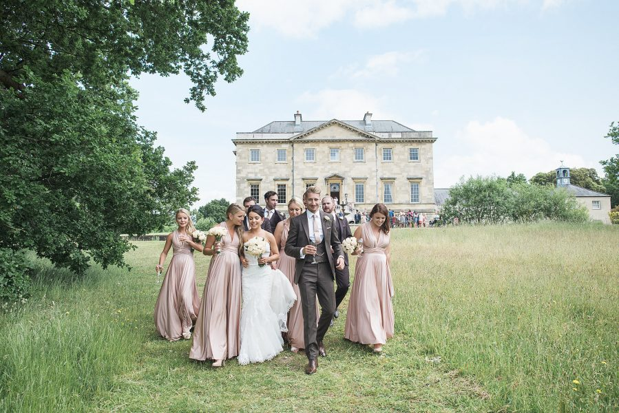 Bride and Groom surrounded by Bridal party joyfully walk together in a buttercup meadow with Botley Mansion Surrey in the background
