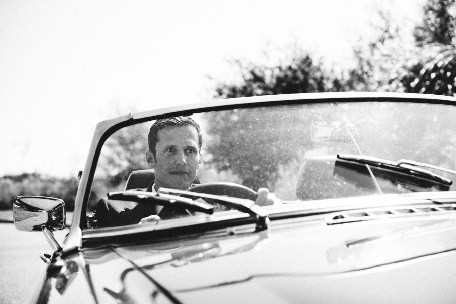 Black and white portrait of Groom behind the wheel of a classic vintage sports car