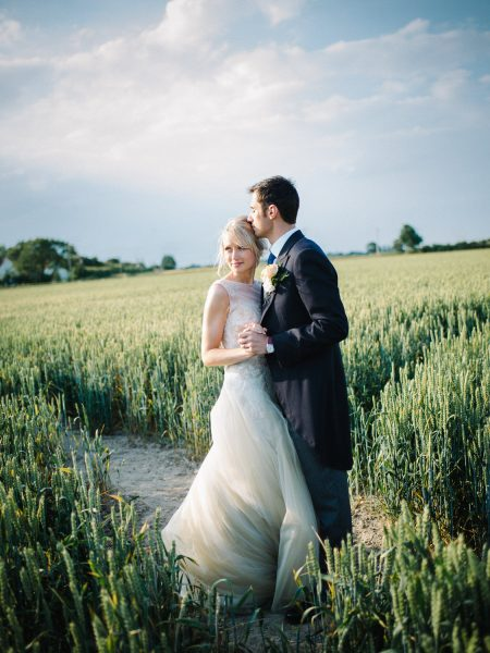 Bride and Groom hold each other close looking into the distance while surrounded by a sunlit field of corn for a relaxed country farm wedding