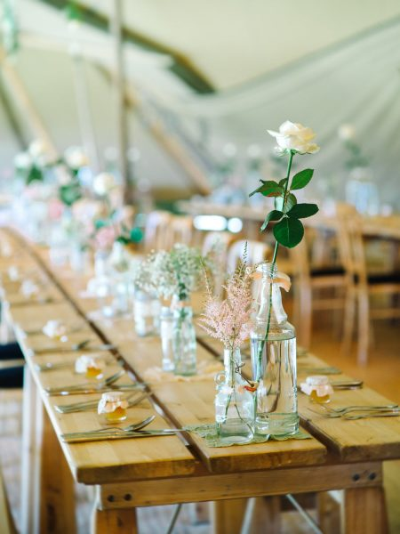 Tipi interior featuring treacle tables and single seemed bottles and jars including for rustic country flowers at farm wedding