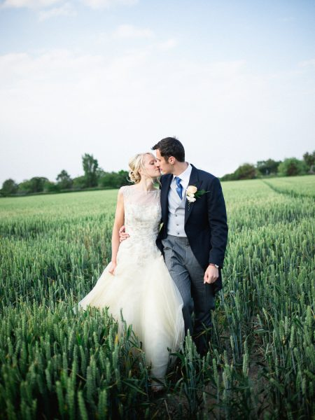 Bride and Groom kiss as they walk along in a sunlit field of corn for a relaxed country farm wedding