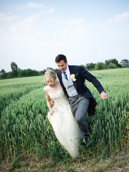 Bride and Groom jump out of corn field giggling during their relaxed country farm wedding