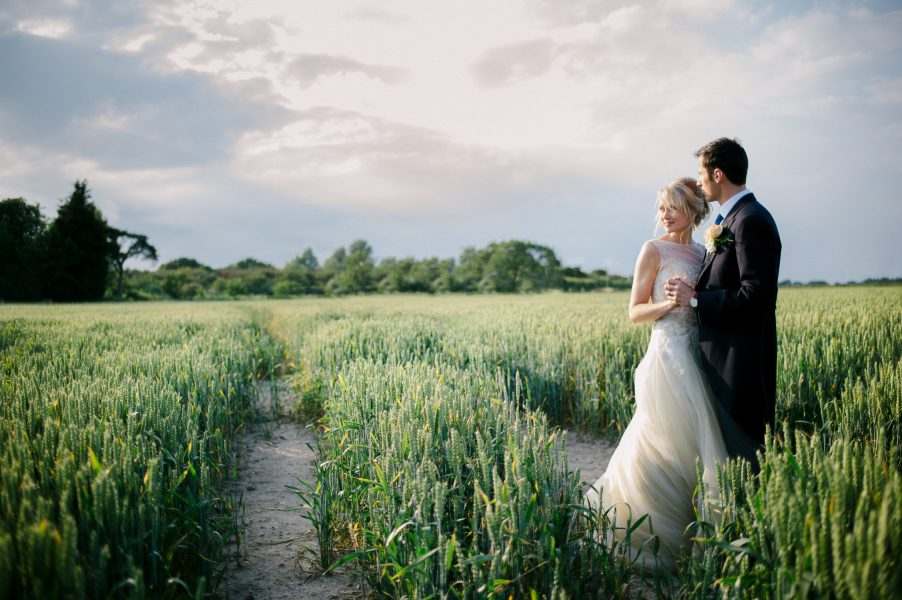 Bride and Groom look dreamily toward the sun in a sunlit field of corn for a relaxed country farm wedding