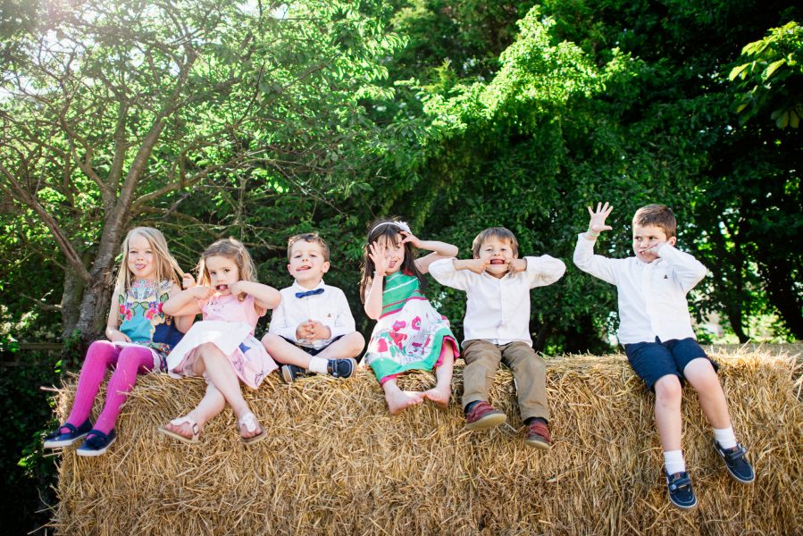 Child guest sit on a hay bale pulling silly faces at the camera at a relaxed country farm wedding