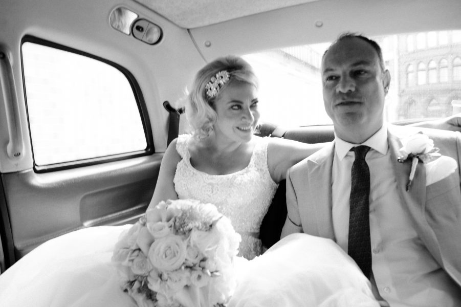 Classic Fine Art Portrait of Bride sitting in back of London taxi in Islington just after their wedding ceremony