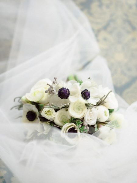 Anemone bouquet with navy ribbon resting on a veil