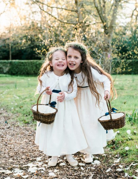 Flower girls hug and smile together as they carry wicker baskets at Larmer tree Gardens Wiltshire during the Golden Hour