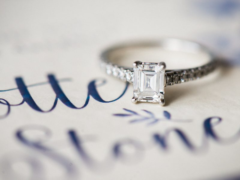 Close up of emerald cut engagement ring on blue invitation calligraphy writing