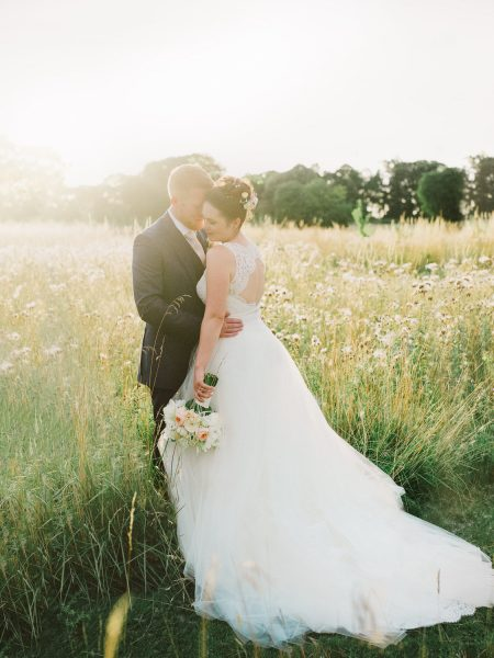 Bride and Groom Fine Art portrait taken during golden hour of Bride and Groom stand together in a beautiful wild grass meadow with the brides dress splaying out behind her catching a setting sun