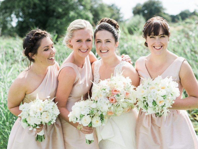 Blush peach mint and cream Bridesmaids surround Bride for a smiley summer wedding portrait holding flowers