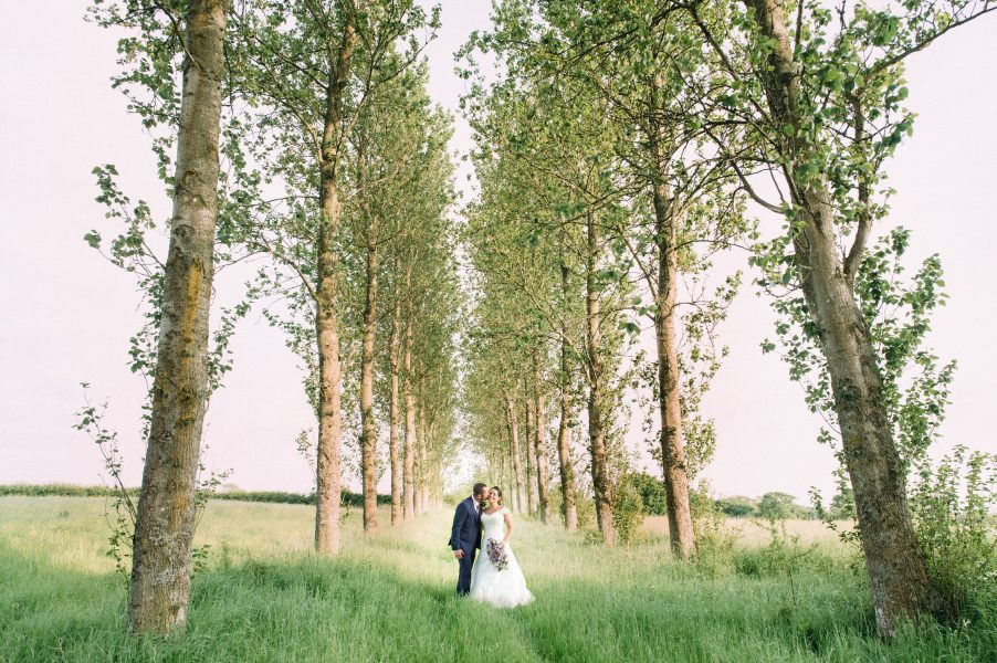 Bride and Groom stand in the middle of an alley to tall surrounded by meadow in Sussex