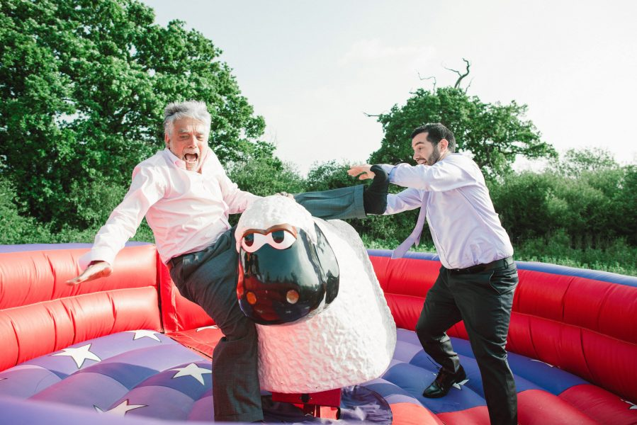 Guest falling off fairground ride sheep in a bright inflatable circle a relaxed country Sussex fairground wedding