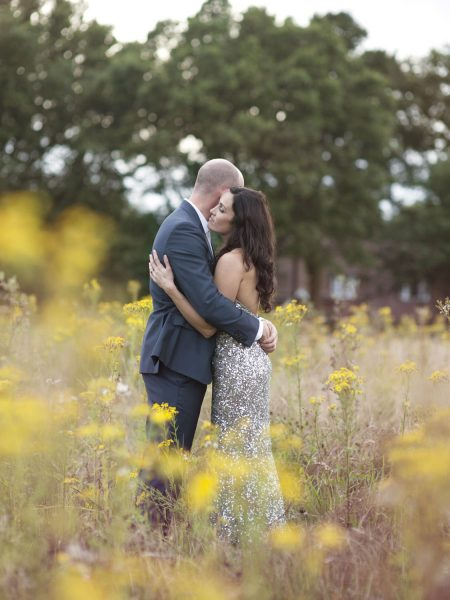 Bride in gold silver sequinned adding dress and Groom in a relaxed hug embrace in a rustic yellow summer meadow a relaxed country back garden wedding