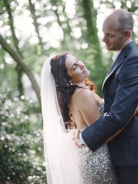 Groom holds Bride in arms in a loving gave as bride in a silver gold sequinned dress and veil leans back in a happy moment set in a forest as part of their relaxed country back garden wedding