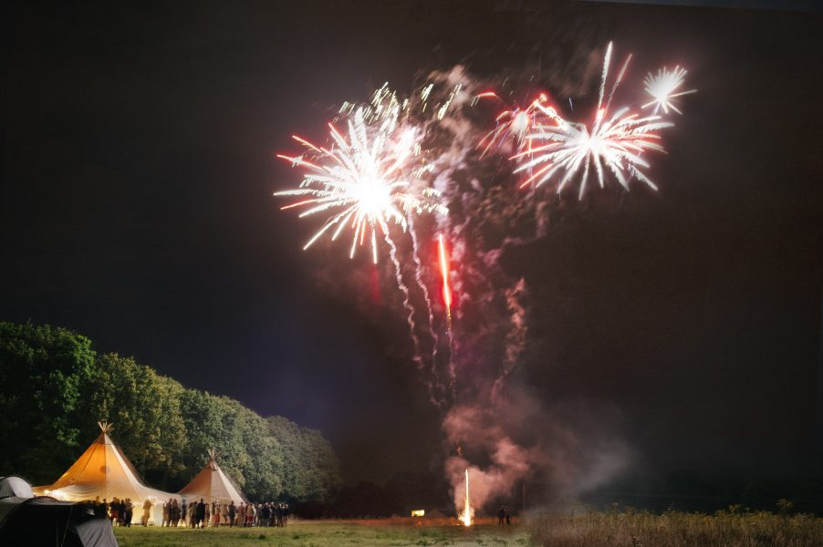 Red Fireworks explode over the tipi as a dramatic end to a relaxed country back garden wedding