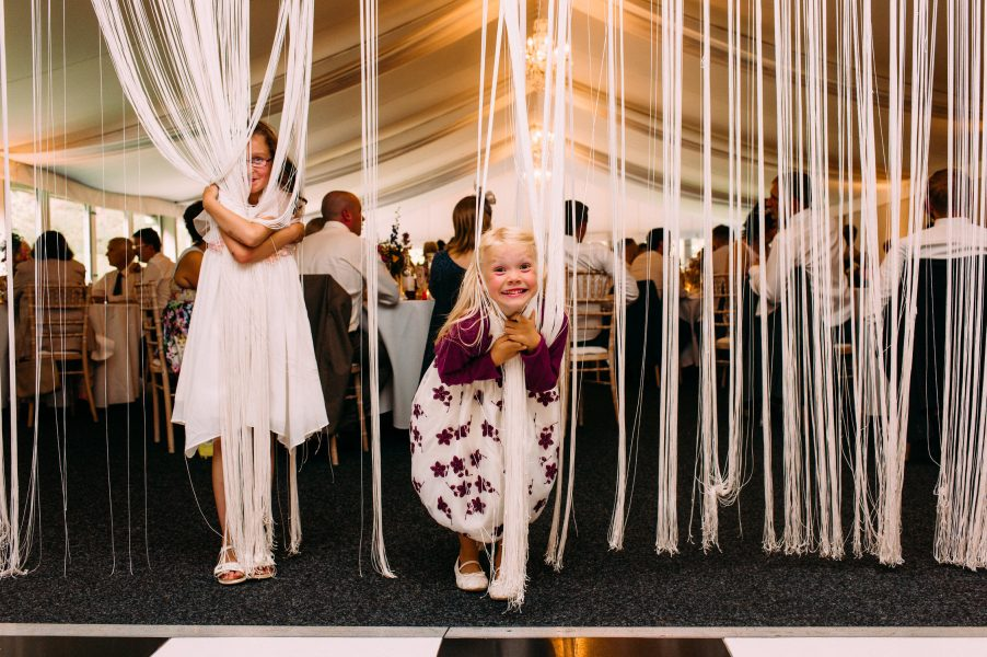 Two young girl wedding guests play in a curtain of fringing hiding behind the cream fringe on the black and white wedding dance floor