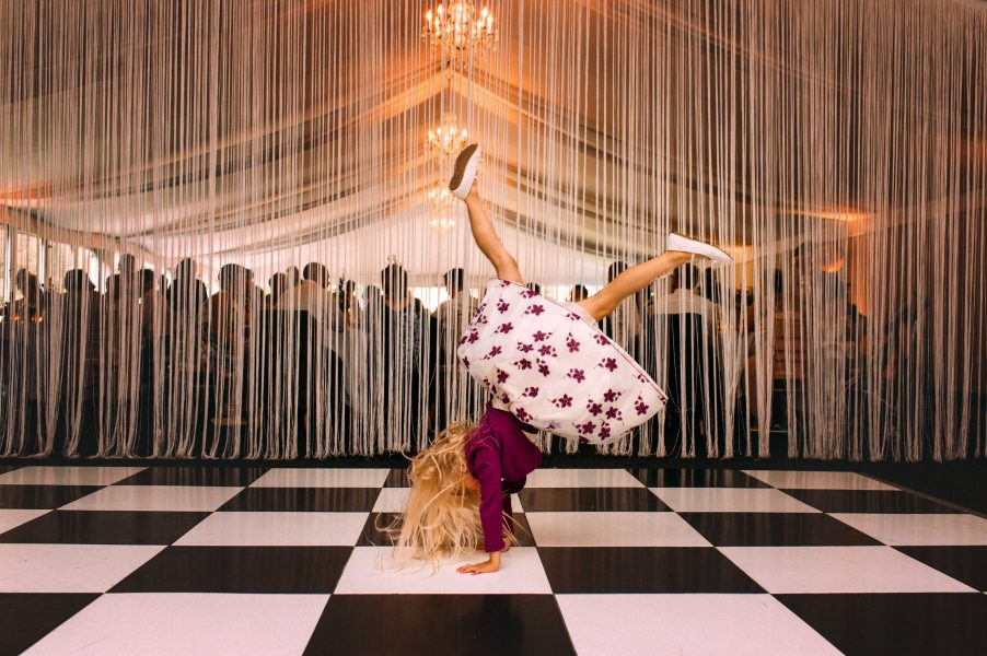 Young girl wedding guest playfully doing a handstand in front of a curtain of fringing on the black and white check wedding dance floor