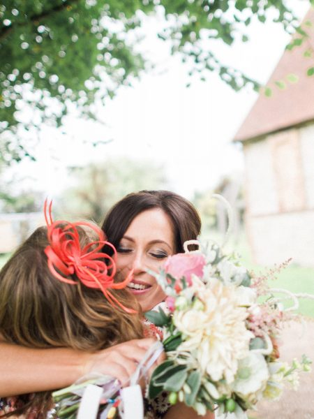 Bride emotionally hugs Bridesmaid holding a rustic bouquet from Catkin & Pussywillow Winchester. Taken at relaxed Summer wedding Tithe Barn Petersfield