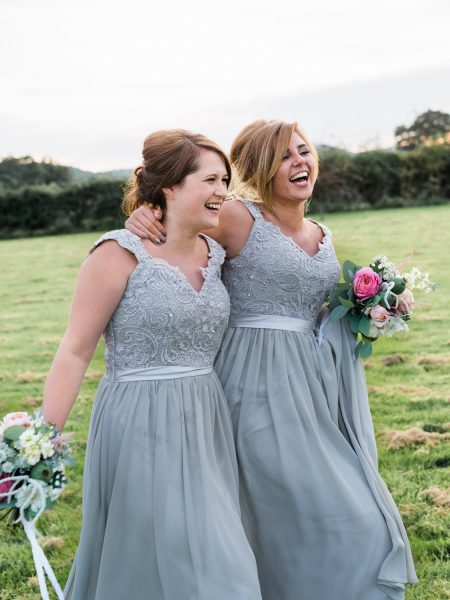 Natural candid moment of Bridesmaids in aqua grey long dresses happily walking through a field laughing. Taken at relaxed Summer wedding Tithe Barn Petersfield