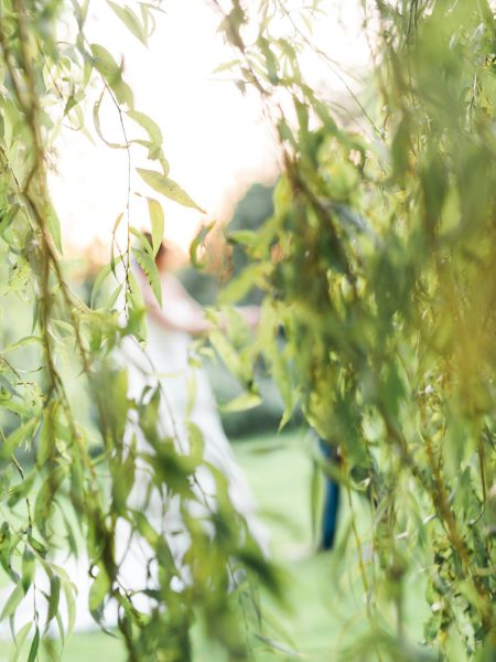 Natural weeping willow abstract image with blurred wedding couple dancing behind green foliage. A moment from a relaxed Summer wedding Tithe Barn Petersfield