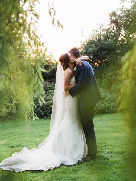 Fine Art Natural moment of Wedding couple embracing as the sun sets framed by a weeping willow. A moment from a relaxed Summer wedding Tithe Barn Petersfield
