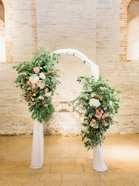 Wedding floral arch of peach blush and pink roses for barn during ceremony. A moment from a relaxed Summer wedding Tithe Barn Petersfield