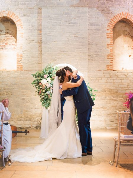 Wedding couple embracing under floral arch during ceremony after first kiss. A moment from a relaxed Summer wedding Tithe Barn Petersfield