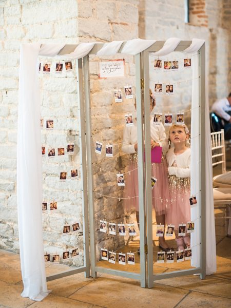 Cute girls in pink and gold sequin dresses look at table setting display made of polaroid photos. A moment from a relaxed Summer wedding Tithe Barn Petersfield