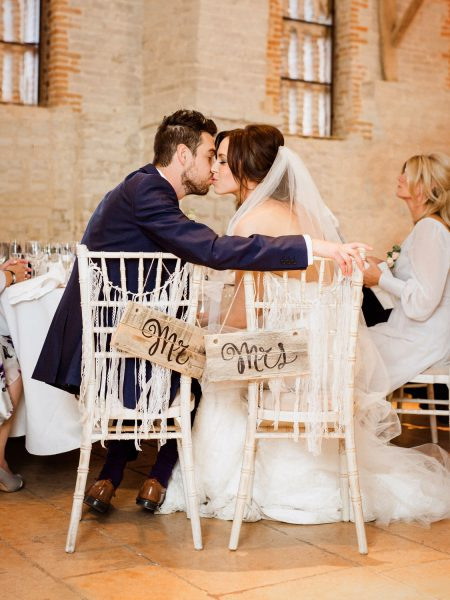 Fine Art Natural moment of Wedding couple kissing in chairs marked Mr and Mrs during their relaxed wedding reception at Tithe Barn Petersfield