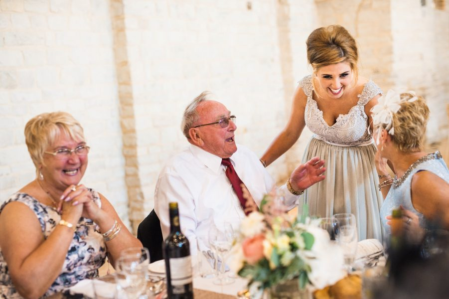 Fine Art Natural moment of wedding guests and bridesmaid laugh at a wedding table during their relaxed wedding reception at Tithe Barn Petersfield