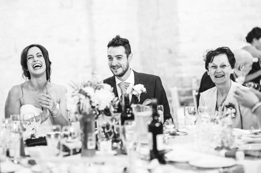 Bride and Groom and family laugh during the speeches at their relaxed wedding reception at Tithe Barn Petersfield